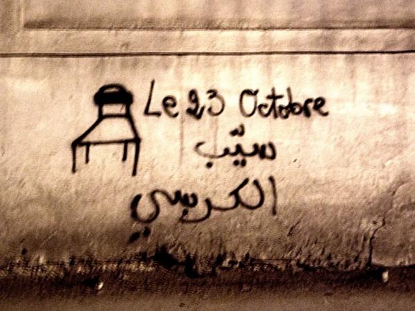 """Da I muri di Tunisi. Segni di rivolta, """"Il 23 ottobre molla la poltrona"""" Il 23 ottobre del 2012, a un anno esatto dalle elezioni del 2011, l'assemblea costituente avrebbe dovuto presentare la nuova costituzione, il governo provvisorio sciogliersi e i tunisini tornare alle urne. In realtà, per tutto ciò, sono passati altri due anni."""