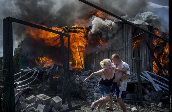 Uno sguardo sul mondo | VALERY MELNIKOV - Black Days of Ukraine. Civili in fuga dall'incendio di una casa distrutta da un attacco aereo nel villaggio di Luhanskaya. © Valery Melnikov