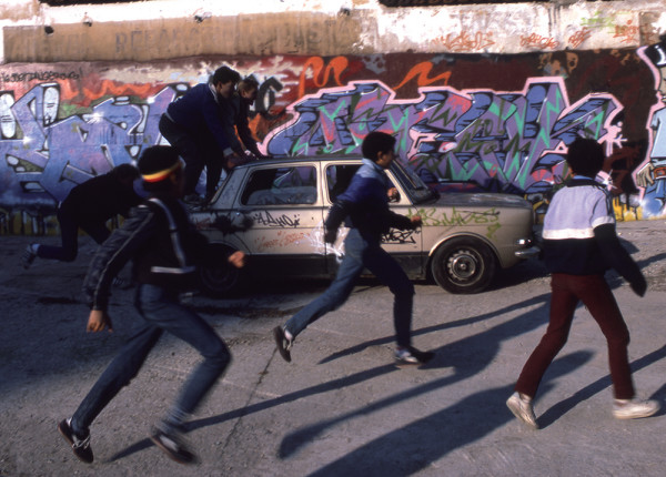 Henry Chalfant, Boys chase abandoned car past St…ll, Paris, 1985
